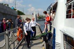 学校的毕业生在莫斯科河的游览中的游船的 库存照片