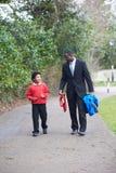 学校的父亲走的儿子沿道路 免版税图库摄影