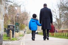学校的父亲走的儿子沿道路 免版税库存照片