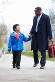 学校的父亲走的儿子沿道路 免版税库存图片