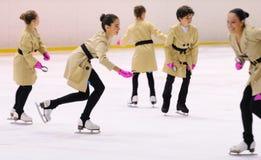 从学校的年轻队滑冰在冰执行,假装作为探员与雨衣,在国际杯Ciutat 免版税图库摄影