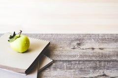 学校笔记本和苹果在木背景 免版税库存照片