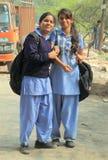 学校衣裳的两个女孩微笑着给某人 免版税图库摄影