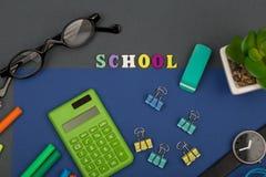 学校设置了与蓝纸、文本& x22; School& x22;木信件、计算器、标志、镜片、手表和其他文具 库存照片