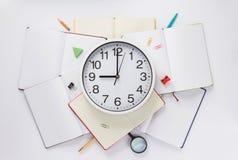 学校辅助部件和壁钟在笔记本 库存照片