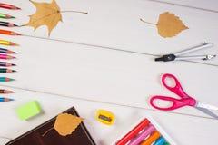 学校辅助部件、书和秋季叶子框架在委员会,回到学校 库存图片