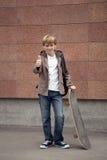 学校青少年与书包和滑板 图库摄影