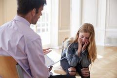 学校顾问谈话与沮丧的母学生 免版税库存照片