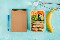 学校饭盒用三明治、蔬菜、水和水果在桌上 图库摄影
