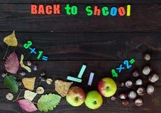 学校主题 秋叶、栗子和成熟苹果在黑暗的木背景 在您的对象的地方上 免版税库存图片