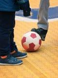 学生与球的儿童游戏橄榄球在校园 免版税库存照片