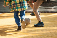 学生与球的儿童游戏橄榄球在校园 免版税库存图片