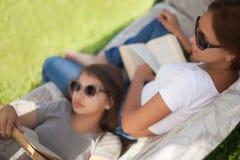 学生业余时间,读的女孩和放松户外 免版税库存图片