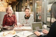 学生为在咖啡馆的检查做准备 免版税图库摄影