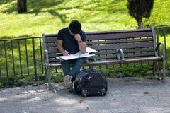 学生为在街道上的类做准备坐长凳 免版税库存照片