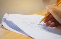 学生候宰栏在采取检查的手上,写考试 免版税库存照片