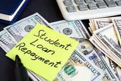 学生借款偿还的金钱在桌上 库存图片