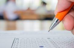 学生做与笔图画selecte的手测试考试 库存照片