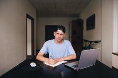 学生做家庭作业工作,当坐在他的家时 十几岁在家学习 看看照相机 库存图片