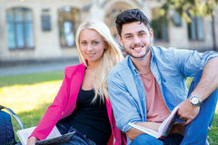 学生友谊 学生夫妇坐草和 免版税库存照片