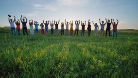 学生向学校说再见 摇他们的手的学生反对落日的背景 免版税图库摄影
