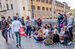 学生听他的老师演讲历史教训在街道坐桥梁Fabricio的路面Tib 免版税库存照片