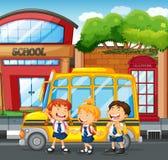 学生和校车在学校 免版税库存照片
