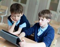 学生和片剂在教室 免版税库存图片