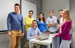 学生和老师有纸和膝上型计算机的 免版税库存图片