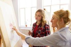 学生和老师有画架的在艺术学校 免版税库存照片