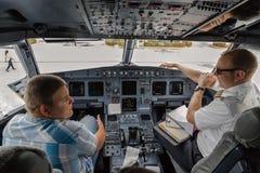 学生和飞行员谈话在平面驾驶舱内 免版税库存照片