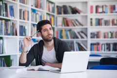 学生在使用膝上型计算机的学校图书馆里研究的 免版税库存图片