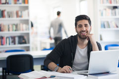 学生在使用膝上型计算机的学校图书馆里研究的 免版税库存照片