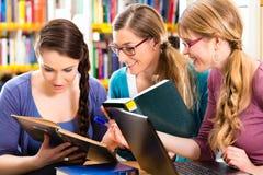 学生在图书馆是一个学习的小组 免版税库存照片