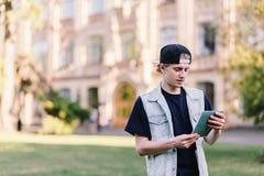 学生在大学的背景站立并且读从他的笔记本的任务 库存图片