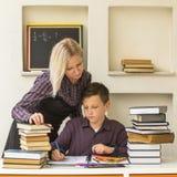 年轻学生在家学会与一位他的家庭教师 教育 免版税图库摄影