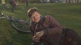学生在度假在公园安排了与苏打和食物的一顿野餐 一个年轻人送啤酒到他的朋友 愉快 股票录像