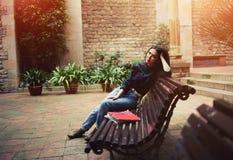 年轻学生坐在一条美丽如画的街道的一条长凳 库存图片