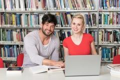 学生夫妇有膝上型计算机的在图书馆里 图库摄影