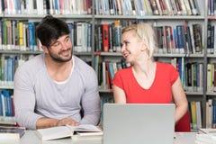 学生夫妇有膝上型计算机的在图书馆里 库存图片