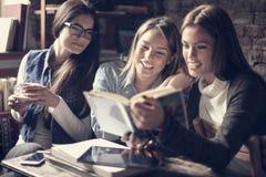 学生女孩一起阅读书在咖啡馆 库存图片