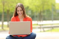 学生女孩与一台膝上型计算机一起使用在一个绿色公园 免版税库存图片