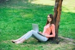 学生女孩与一台膝上型计算机一起使用在一个绿色公园 库存照片