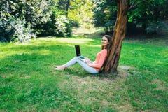 学生女孩与一台膝上型计算机一起使用在一个绿色公园 图库摄影