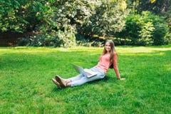 学生女孩与一台膝上型计算机一起使用在一个绿色公园 库存图片