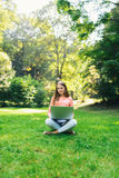 学生女孩与一台膝上型计算机一起使用在一个绿色公园 免版税图库摄影