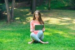 学生女孩与一种片剂一起使用在一个绿色公园 库存图片