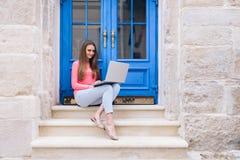 学生女孩与在蓝色门前面的一台膝上型计算机一起使用 库存图片
