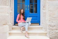 学生女孩与在蓝色门前面的一台膝上型计算机一起使用 免版税库存照片