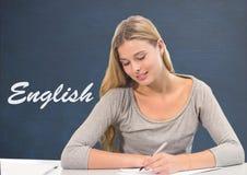 学生女孩在反对蓝色黑板的桌上有英国文本的 免版税库存图片